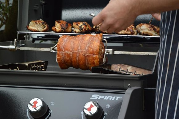 Weber spirit barbecue with stuffed joint of pork on rotisserie and chicken fillets