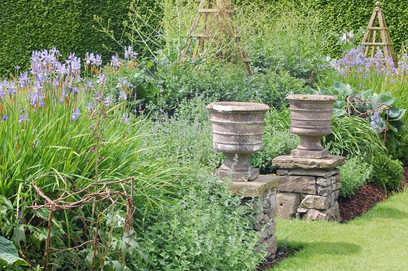herbaceous border with urns at Levens Hall, Cumbria