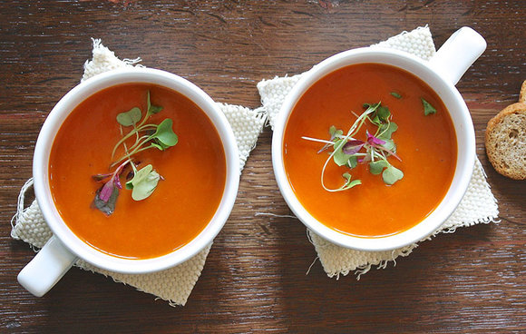 two bowls of tomato soup with a garnish of micro-herbs