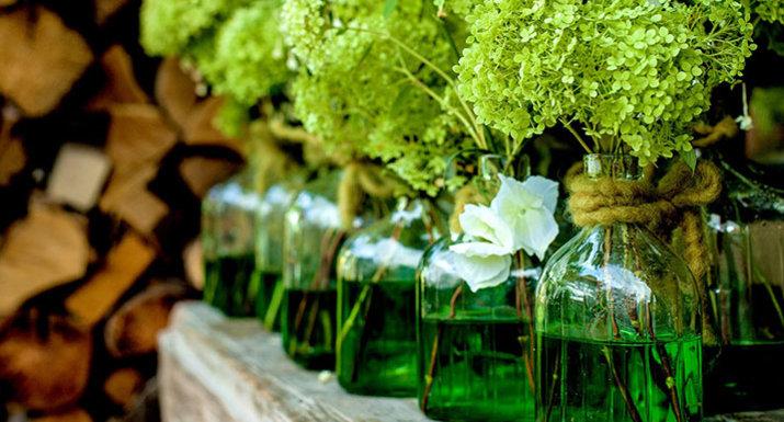 Flower heads in green glass vases
