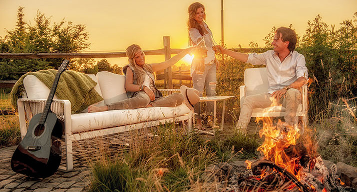 People sitting outside on garden furniture around a fire