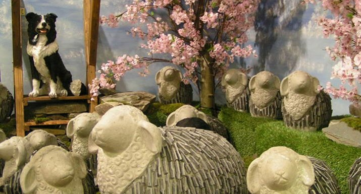 Flock of stone sheep with sheepdog