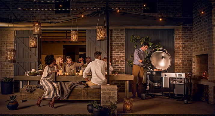 Weber Summit charcoal grilling centre on patio with party of people