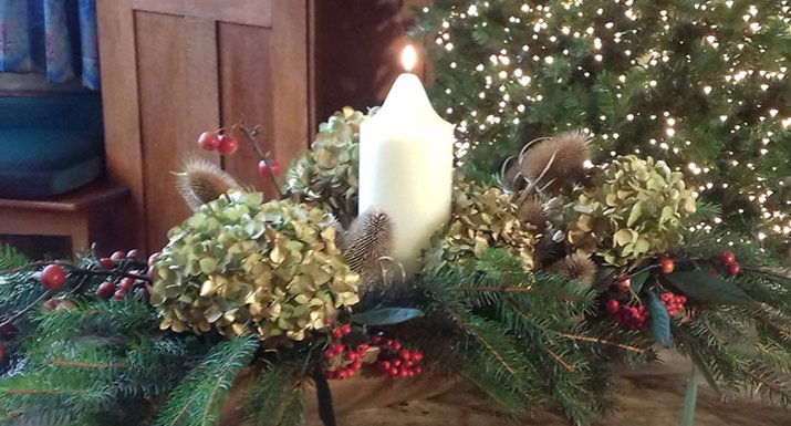 Christmas table arrangement with church candle, conifer, hydrangea, teasel, crab