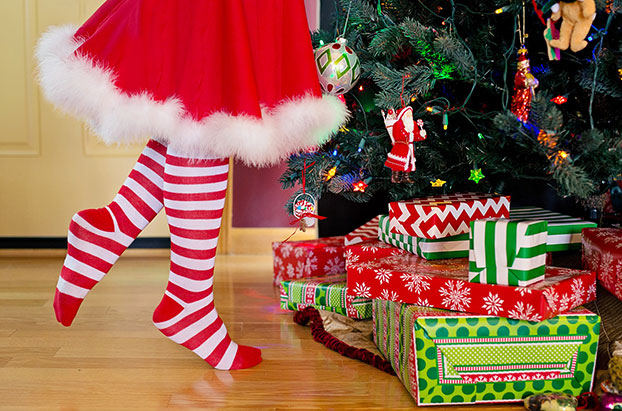 girl in Santa outfit with Christmas tree & presents