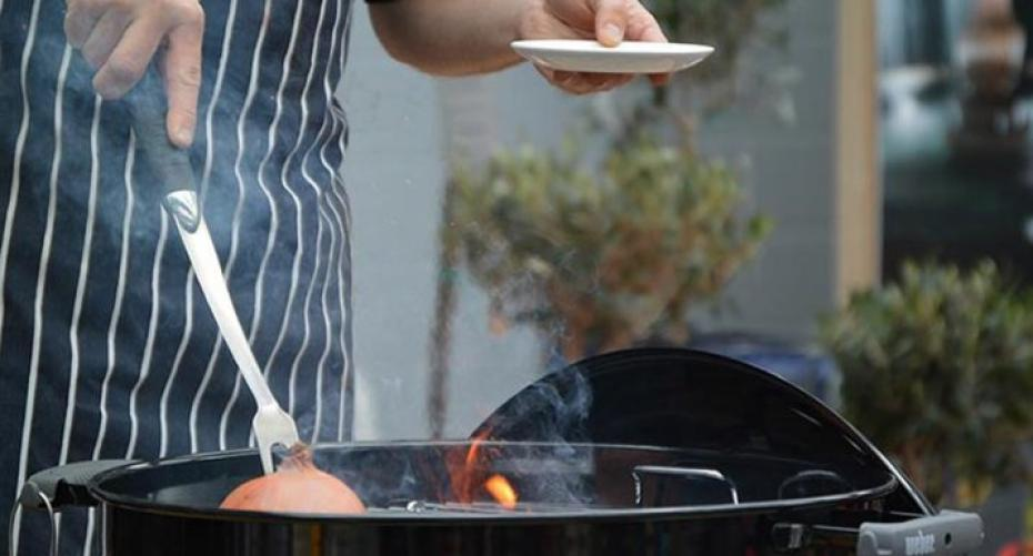 Flavouring a gas BBQ grate with onion dipped in oil