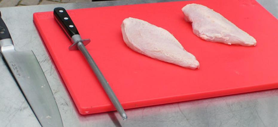 chicken breasts on chopping board with knife and sharpening steel