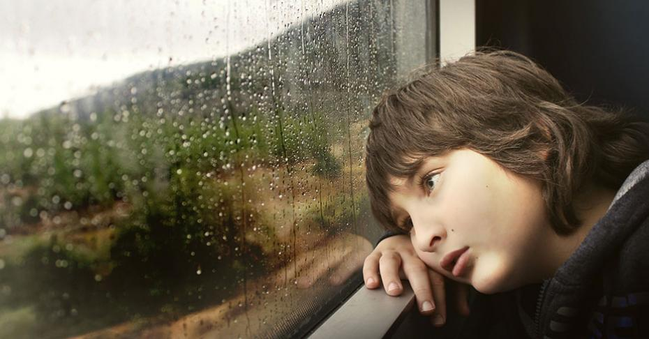young boy looking out of window at the rain