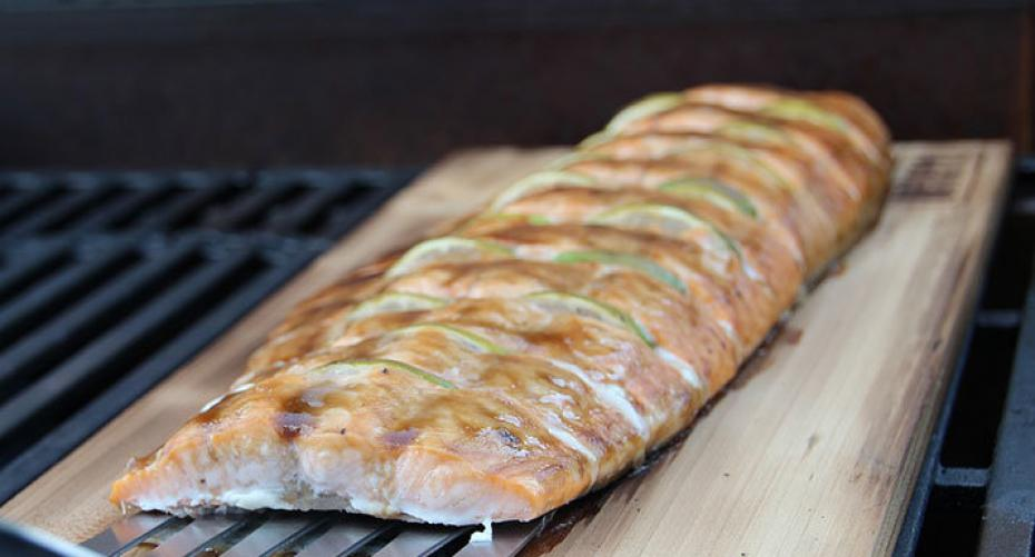 salmon barbecuing on a plank of wood