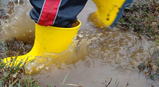 Child with yellow wellies jumping in puddle