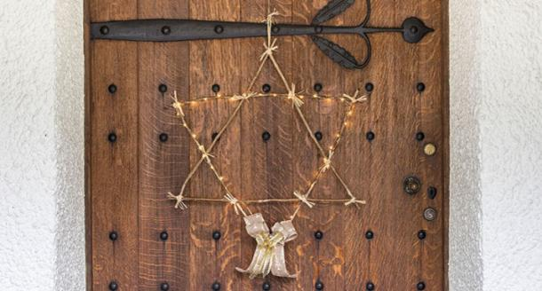 Hand-made lighted twig star hanging on a door