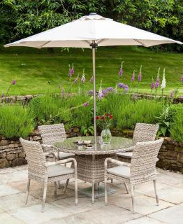 A light coloured woven 4 seater dining set with parasol & base.