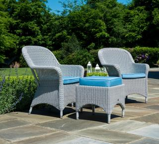This traditional low maintenance set features curved resin weave armchairs with a woven table.