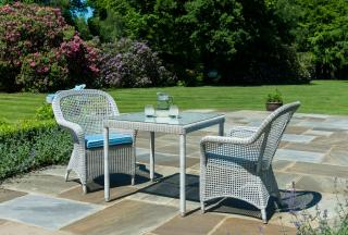 This low maintenance set for two features two armchairs with an open weave & a square woven table.