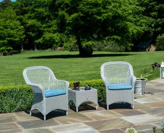 This traditional low maintenance set features curved resin open weave armchairs with a woven table.