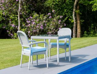 This low maintenance set for two features stacking resin weave armchairs with a square woven table.