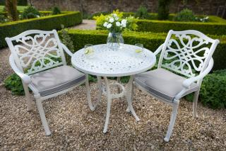 A neutral cast aluminium bistro set finished in Royal White with Weatherready® cushions in Pewter.