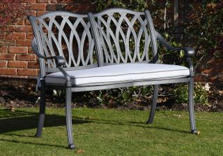 An attractive patterned cast aluminium bench finished in antique grey with a Weatherready® seat cushion in platinum.