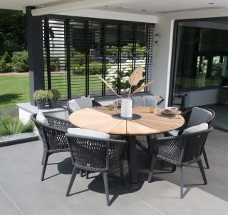 An impressive round teak dining set for six with an interesting cross table base in aluminium accompanied by aluminium & braided rope chairs in anthracite.