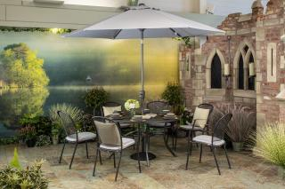 The Caredo 6 Seater Round Set is durable and maintenance free & comes with cushions in Silver Check & parasol in Silver.