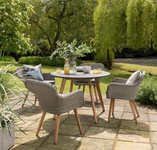 An attractive mixed media dining set for four with Acacia legs, woven chairs & poly-cement table top.