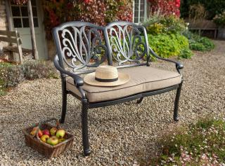 A cast aluminium bench finished in bronze with a Weatherready® cushion.
