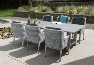 An attractive grey Hularo Weave rectangular dining set with a ceramic top table & all weather cushions.