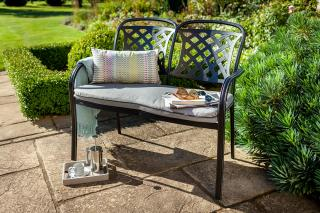 A cast aluminium bench finished in Midnight black with a Weatherready® seat cushion in Shadow.