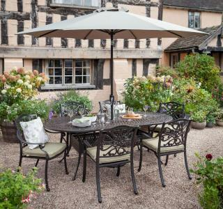 A cast aluminium, oval garden set finished in bronze with Weatherready® cushions in Wheatgrass.