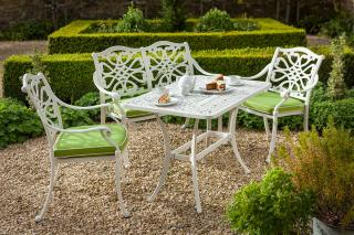 A cast aluminium 4 seat set finished in Royal White with Weatherready® cushions in Lime.