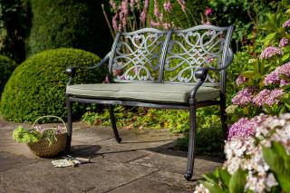 A cast aluminium bench for two, finished in bronze with a Weatherready® cushion in Wheatgrass.