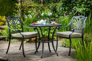 A cast aluminium bistro set finished in bronze with Weatherready® cushions in Wheatgrass.