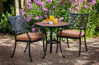 A nature inspired cast aluminium bistro set finished in bronze with a painted concrete table top & matching ® seat cushions in Pumpkin.