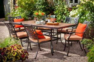 A decorative cast aluminium set for six, finished in bronze with a painted concrete table top & matching Weatherready® seat cushions in Pumpkin.