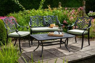 A cast aluminium 4 seat set finished in bronze with Weatherready® cushions in Wheatgrass.