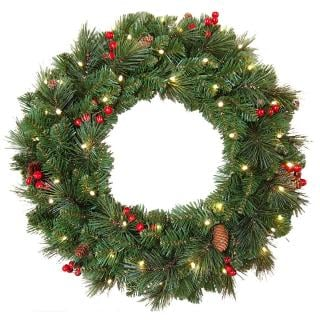 An attractive wreath with bright red berries, pine cones & battery operated lights wound through its PVC branches.