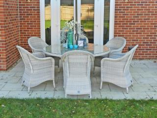 A family sized Hularo dining set in a light Provance weave with all weather seat cushions.