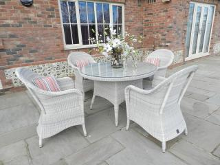 A graceful Hularo dining set in a light Provance weave with all weather seat cushions.