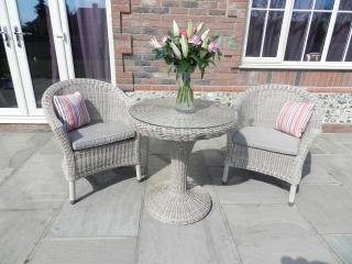 A generous Hularo Weave bistro set with all weather seat cushions in taupe.