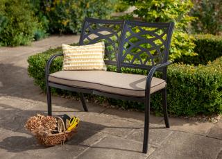 A cast aluminium bench finished in Bronze with a Weatherready® seat cushion in Amber.