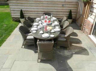A spacious Hularo Weave dining set in Polyloom Taupe for eight with all weather cushions.