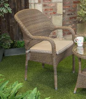 A curvy Hularo Weave stacking chair in Polyloom Taupe with all weather cushion in London Taupe.