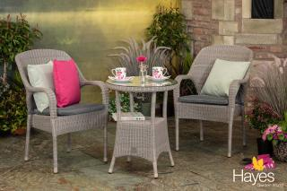 A round Hularo Weave tall tea for two in Polyloom Pebble with stacking armchairs & a glass topped table.