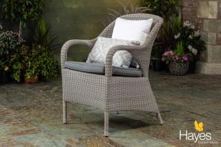 A curvy Hularo Weave dining chair in Polyloom Pebble with all weather cushion in anthracite grey.