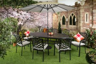 A large oval cast aluminium set for six with parasol & base finished in black with grey cushions.