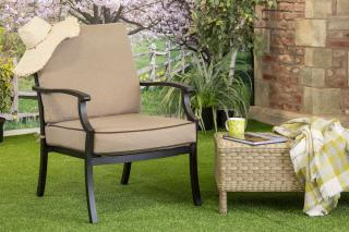 A cast aluminium lounge chair finished in bronze with deep cushions in Desert.