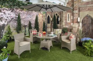 An attractive resin weave dining set for four in an olive tone weave with all weather seat cushions in Taupe.