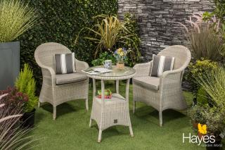A graceful Hularo bistro set in a light Provance weave with all weather seat cushion.