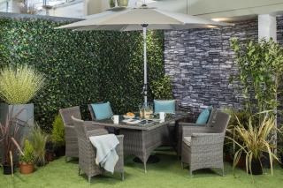 A rectangular 1.7m resin weave dining set for six with a parasol & base.