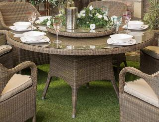 A large family Hularo Weave dining table in Polyloom Taupe with a glass top.